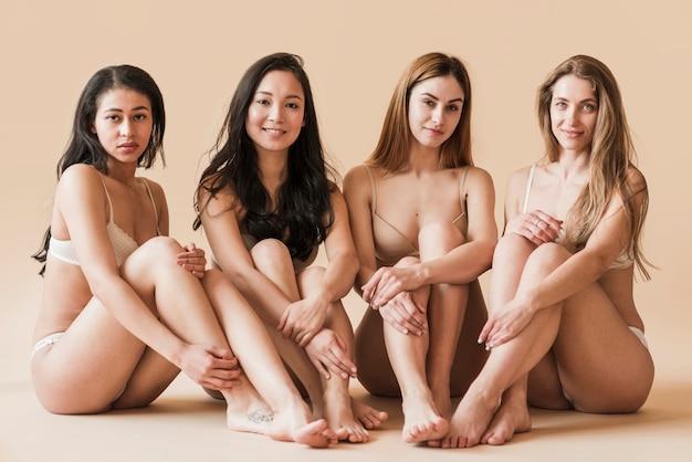 Groep van aantrekkelijke jonge vrouwen in ondergoed zitten in de studio
