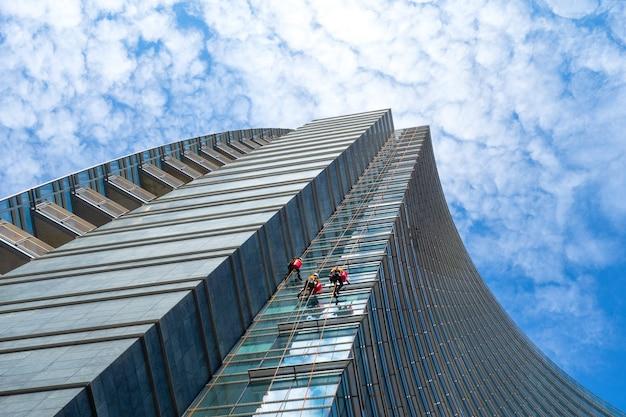 Groep van alpinisten in dienst voor ramenreiniging van wolkenkrabbersgebouwen