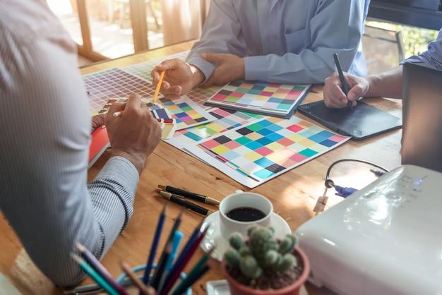 Groep van aziatische ontwerpers brainstormen samen te werken met collega's en kleurstalen