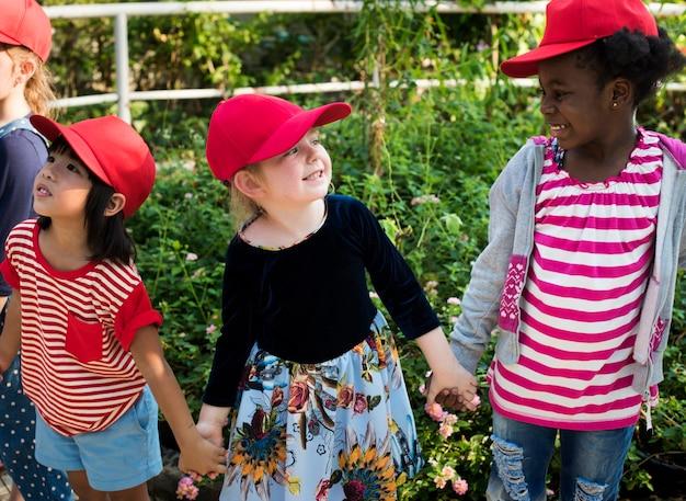 Groep van de school buitentochten van kinderen die in openlucht botanisch park leren