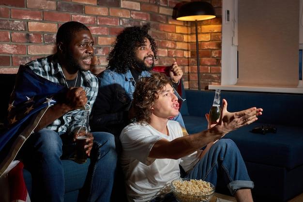 Groep van diverse mannen zittend op de bank kijken naar sport championship samen emotioneel reageren op spelproces, gebaren, bier drinken, thuis