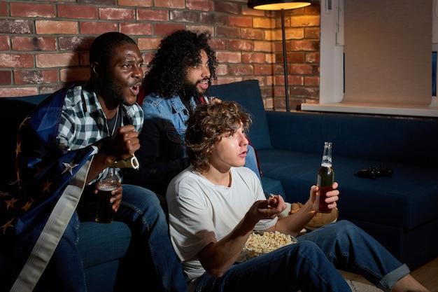 Groep van diverse mannen zittend op de bank kijken naar sportkampioenschap samen emotioneel reageren op spelproces, bier drinken, thuis at