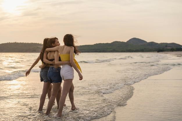 Groep van drie aziatische jonge vrouwen die op strand lopen