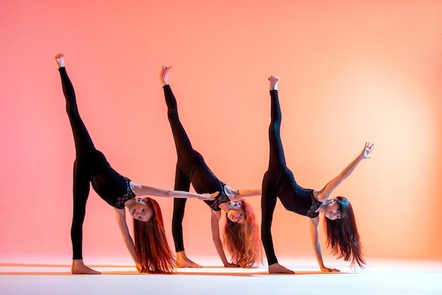 Groep van drie balletmeisjes in zwarte strakke pakken dansen op een rode achtergrond