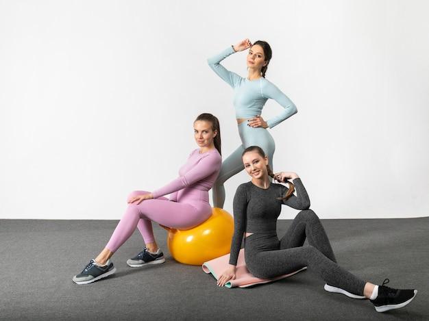 Groep van drie fitnessvrouwen in sportkleding die op witte achtergrond stellen