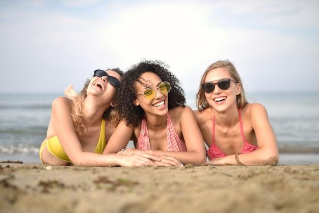 Groep van drie glimlachende jonge vrouwen op het strand het concept geluk