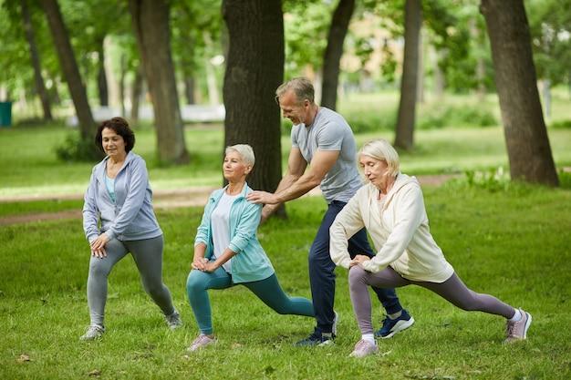 Groep van drie hogere vrouwen die ochtend samen in park doorbrengen die oefeningen doen met hun trainer die hen helpt