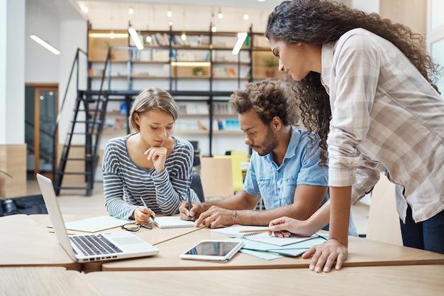 Groep van drie jonge multi-etnische succesvolle zakenmensen zitten in coworking ruimte, praten over nieuw project van concurrent team, plannen maken om hun project te omzeilen.