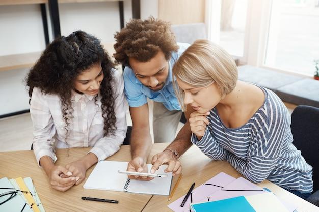 Groep van drie jonge ondernemers die samenwerken aan nieuw startup project. jongeren die in bibliotheek zitten die door informatie over smartphone kijken.