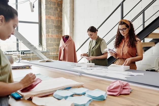 Groep van drie jonge ontwerpers van kleding staan bij grote tafel in werkplaats en kijken door monsters van stof en andere dingen