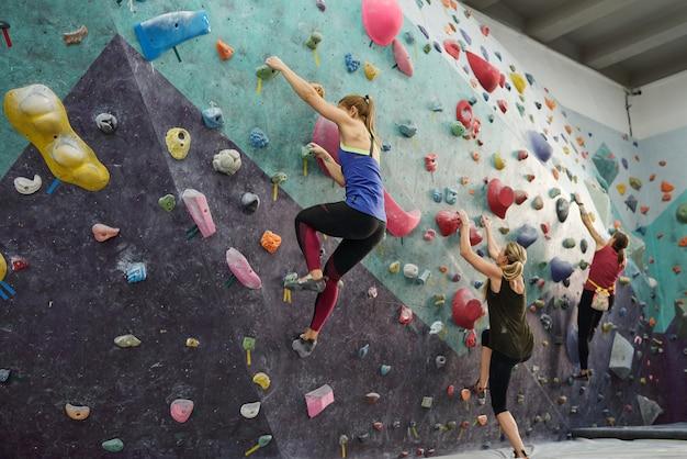 Groep van drie jonge sportvrouwen in activewear klimmen op de muur terwijl ze bij kleine rotsen grijpen tijdens training in de sportschool