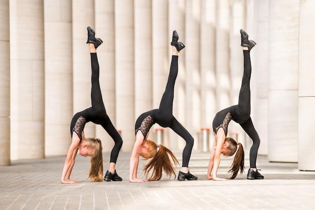 Groep van drie kleine ballerina's in zwarte strakke kostuums dansen tegen de achtergrond van stadsgezicht.