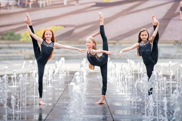 Groep van drie kleine ballerina's in zwarte strakke pakken dansen op een warme dag tegen de achtergrond van stadsfonteinen.