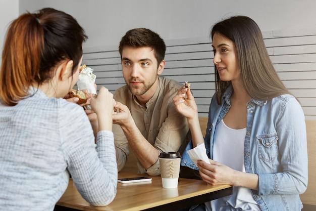 Groep van drie knappe studenten zitten in de kantine van de universiteit, lunchen, praten over gisteren examens. universitair leven.