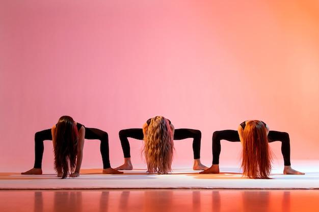 Groep van drie meisjes in zwarte strakke pakken dansen op een rode achtergrond