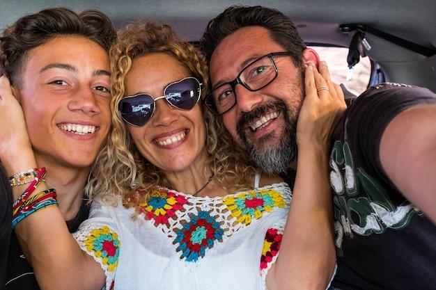 Groep van drie mensen samen in de auto die plezier hebben en een selfie maken - gelukkige familie die naar de camera kijkt