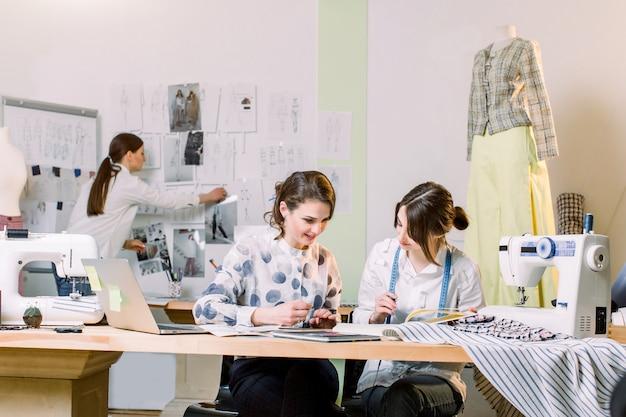 Groep van drie mooie vrouwen fasion ontwerpers werken met kleding tekeningen aan de tafel met op maat tools en laptop