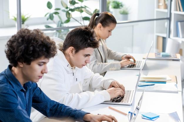 Groep van drie tienerstudenten die in rij door bureau zitten en laptopvertoningen bekijken terwijl individueel aan les op universiteit werken