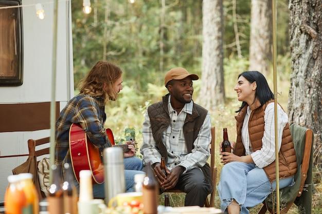 Groep van drie vrienden die genieten van buiten kamperen met een aanhangwagen en bier drinken