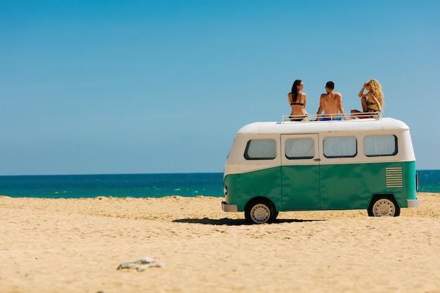 Groep van drie vrienden genieten van zonnige dagen op hippie auto