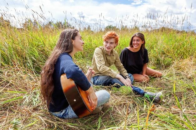 Groep van drie vrienden met gitaar zingen lied buitenshuis