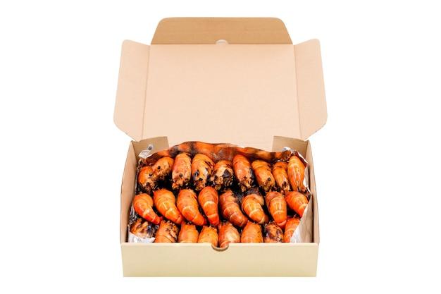 Groep van gegrilde riviergarnalen regelen in een kartonnen doos geïsoleerd op een witte achtergrond.