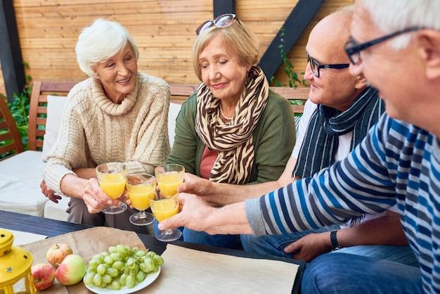 Groep van gepensioneerde vrienden roosteren tijdens de lunch