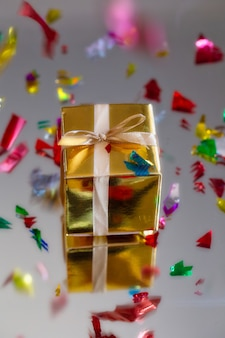 Groep van gouden sprankelende geschenkdozen op grijze achtergrond met reflectie en confetti
