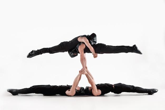 Groep van gymnastiek acrobatische blanke mannen per saldo poseren