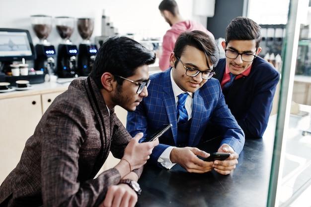Groep van indische zakenman drie in kostuums die op koffie zitten en op mobiele telefoon kijken.