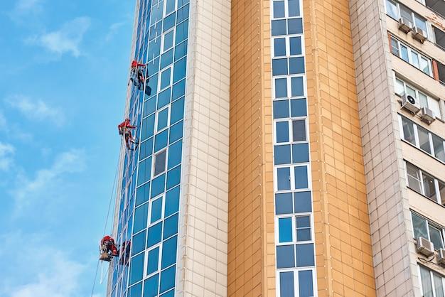 Groep van industriële klimmer werken op een modern gebouw buiten