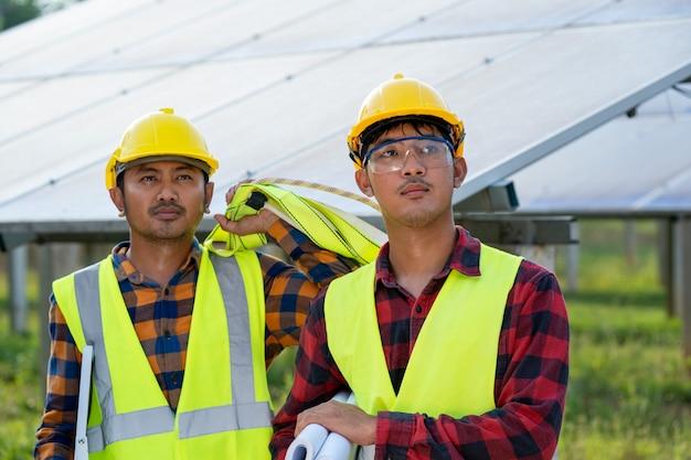 Groep van ingenieurs die zonnepaneel controleren in routinematige werking bij zonne-energiecentrale, bediening en onderhoud in zonne-energiecentrale, zonne-energiecentrale voor innovatie van groene energie voor het leven.