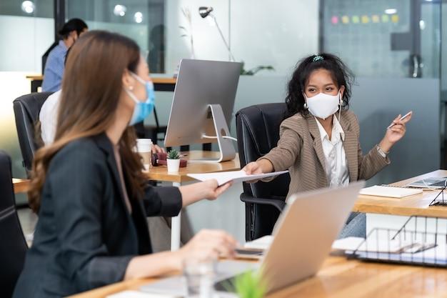 Groep van interraciale bedrijfsmedewerkers draagt een beschermend gezichtsmasker in een nieuw normaal kantoor en oefent op sociale afstand met handdesinfecterend alcoholgel op tafel om verspreiding van coronavirus covid-19 te voorkomen