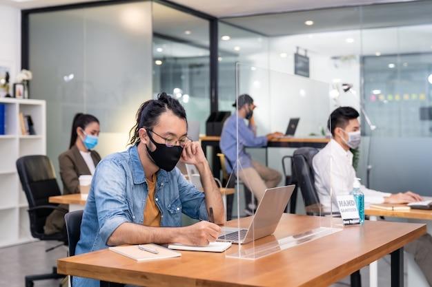 Groep van interraciale bedrijfsmedewerkers draagt een beschermend gezichtsmasker in een nieuw normaal kantoor