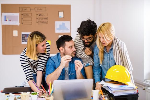 Groep van jonge creatieve ontwerpers staan boven een tafel een praten over problemen op hun werk.
