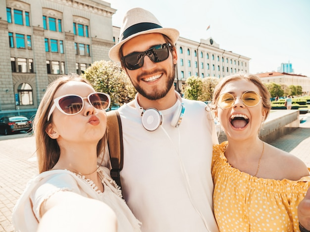 Groep van jonge drie stijlvolle vrienden in de straat. man en twee schattige meisjes gekleed in casual zomerkleding. lachende modellen plezier in zonnebril. vrouwen en jongen foto selfie maken op smartphone