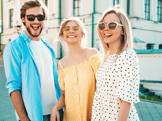 Groep van jonge drie stijlvolle vrienden poseren in de straat. mode man en twee schattige meisjes gekleed in casual zomerkleding. glimlachende modellen die pret in zonnebril hebben. vrolijke vrouwen en kerel bij susnet