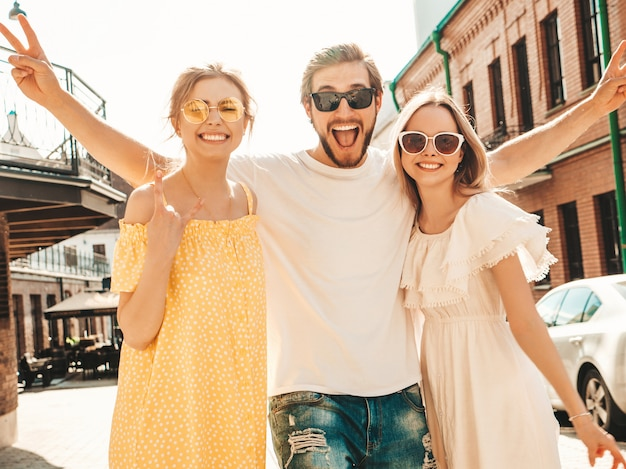 Groep van jonge drie stijlvolle vrienden poseren in de straat. mode man en twee schattige meisjes gekleed in casual zomerkleding. glimlachende modellen die pret in zonnebril hebben. vrolijke vrouwen en kerel die gek worden