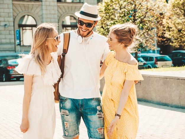 Groep van jonge drie stijlvolle vrienden poseren in de straat. mode man en twee schattige meisjes gekleed in casual zomerkleding. glimlachende modellen die pret in zonnebril hebben. vrolijke vrouwen en kerel het babbelen