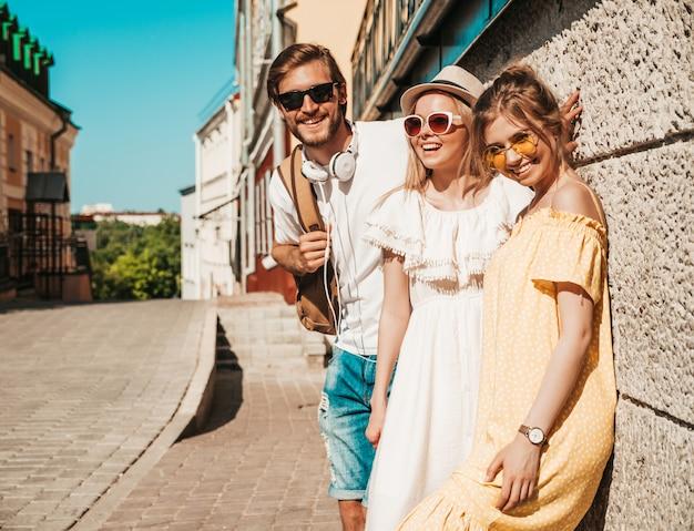 Groep van jonge drie stijlvolle vrienden poseren in de straat. mode man en twee schattige meisjes gekleed in casual zomerkleding. glimlachende modellen die pret in zonnebril hebben. vrolijke vrouwen en kerel in openlucht