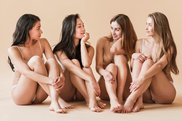 Groep van jonge vrolijke vrouwen in ondergoed zittend op de vloer