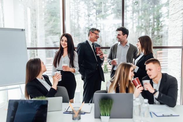 Groep van jonge zakenlui op pauze in office. succesvol commercieel team dat op koffiepauze spreekt. jonge glimlachende collega's op onderbreking het drinken koffie babbelend in modern bureau. zakelijke levensstijl