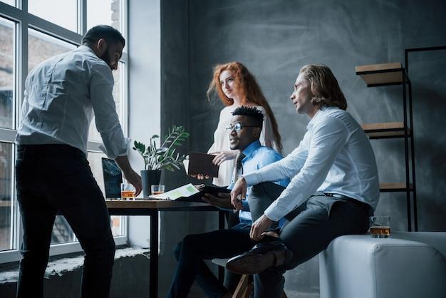Groep van kantoormedewerkers in formele kleding praten over taken en plannen