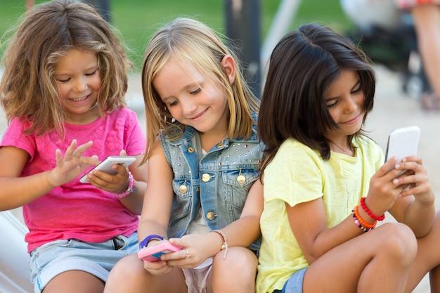 Groep van kinderen chatten met slimme telefoons in het park.