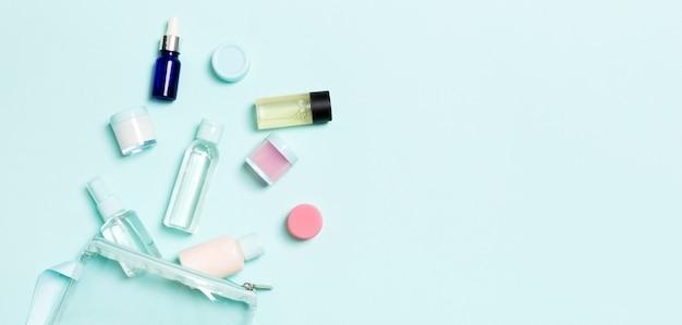 Groep van kleine flesjes voor reizen op blauwe achtergrond. kopieer ruimte voor uw ideeën. plat lag samenstelling van cosmetische producten.
