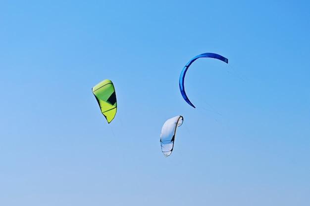 Groep van kleurrijke vliegers van kiteboarding vliegt in de blauwe lucht