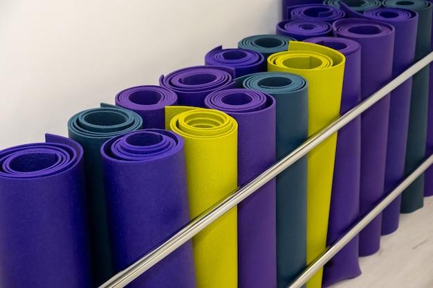 Groep van kleurrijke yoga mat close-up achtergrond. blauwe en groene yogamat in yogaclub, klaslokaal. sport en gezond concept