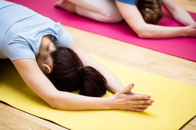 Groep van mensen die het uitvoeren childs pose yoga oefening