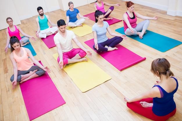 Groep van mensen en trainer zittend in lotushouding