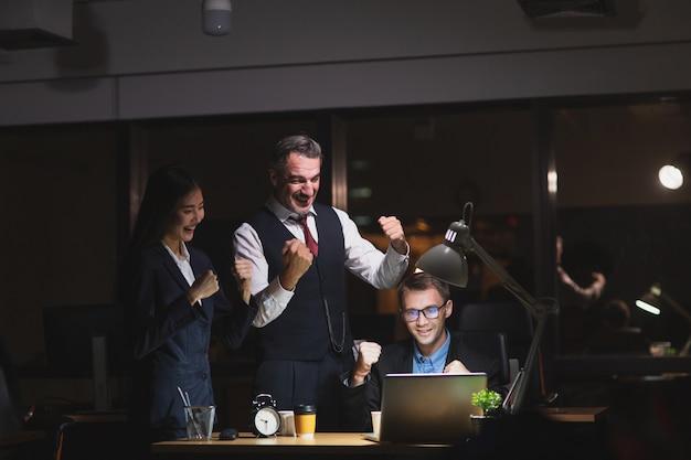 Groep van mensen uit het bedrijfsleven diversiteit laat in kantoor 's nachts werken.